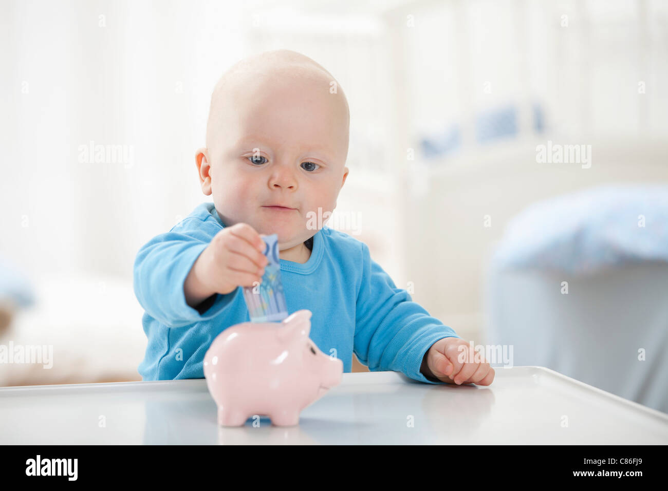 Baby boy putting money in piggy bank - Stock Image