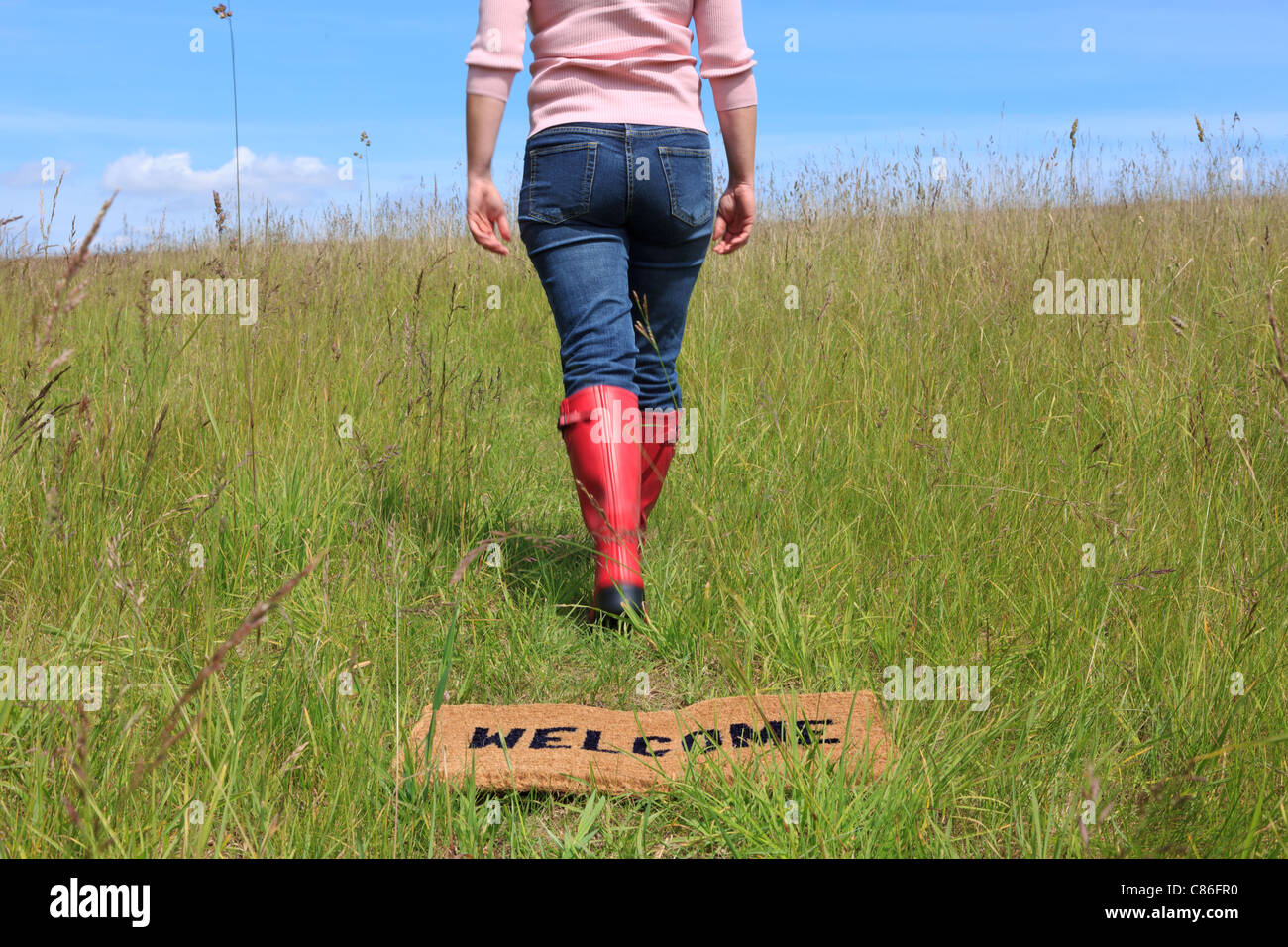 Photo of a woman walking across a welcome mat in a grassy field on a bright sunny day with blue sky. - Stock Image
