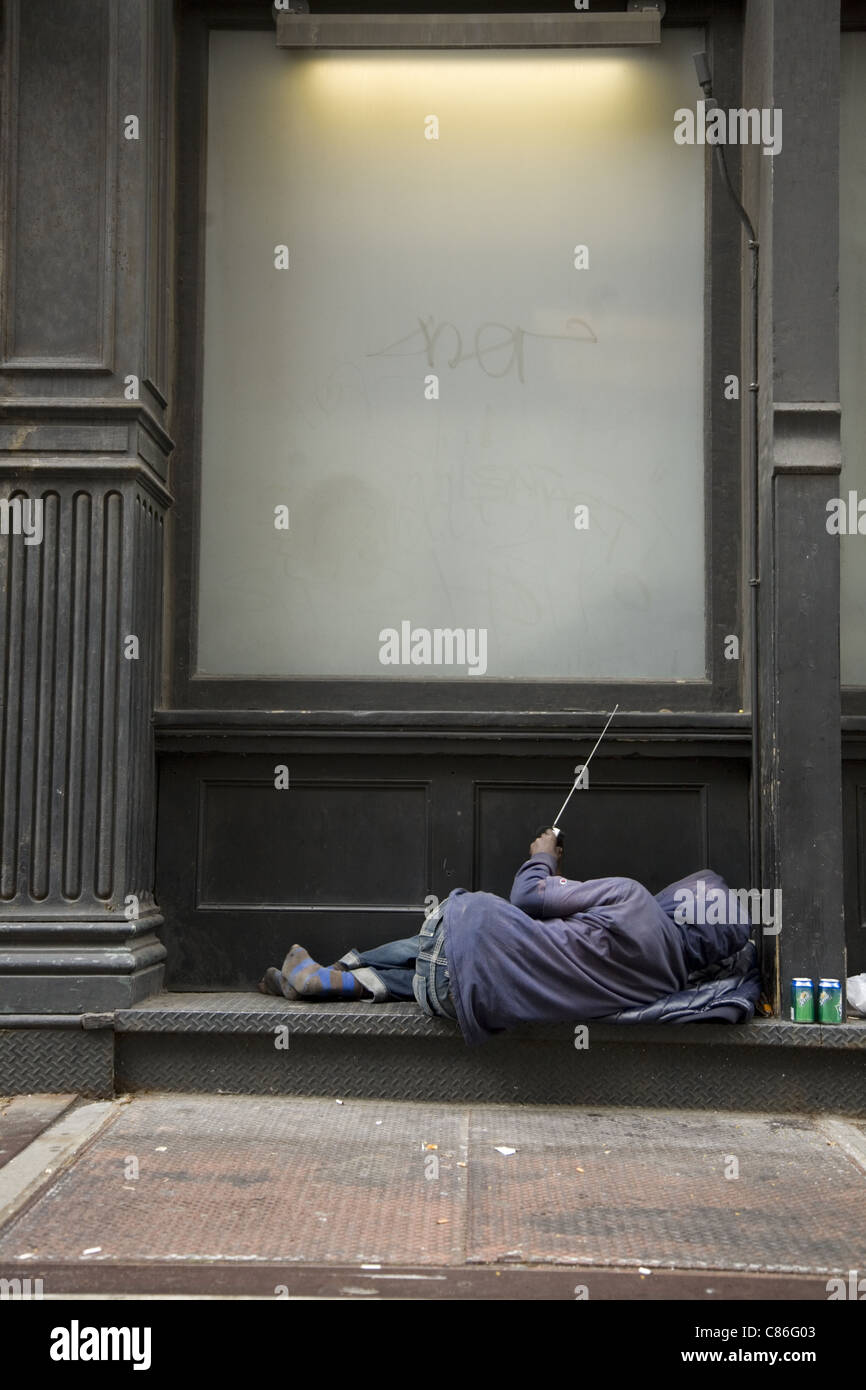 Homeless man adjusts his portable radio in his impromptu bed on 18th St. in NYC. - Stock Image