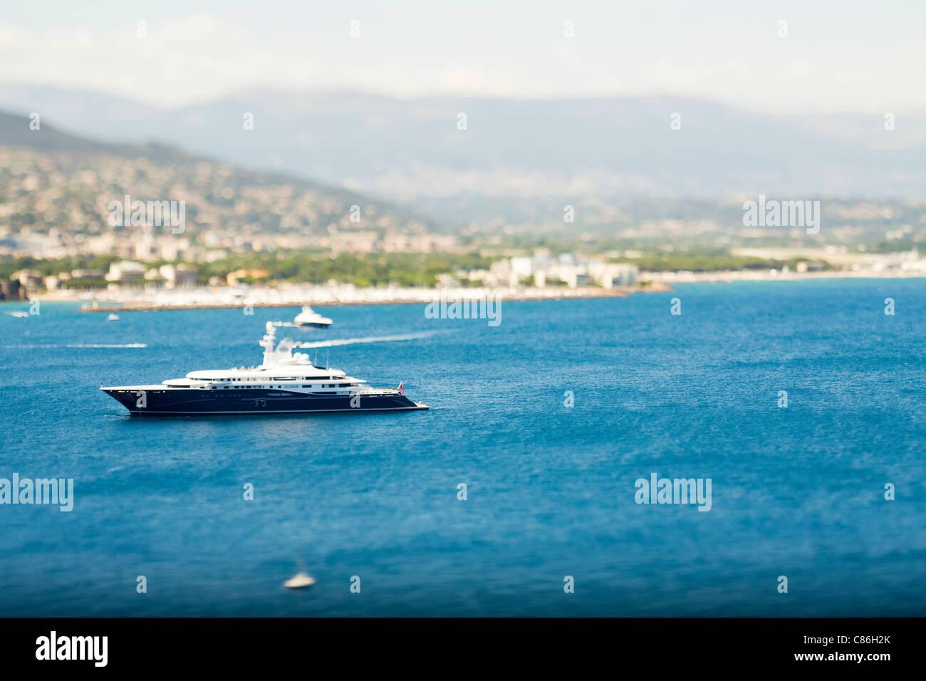 Yacht sailing by urban coastline - Stock Image