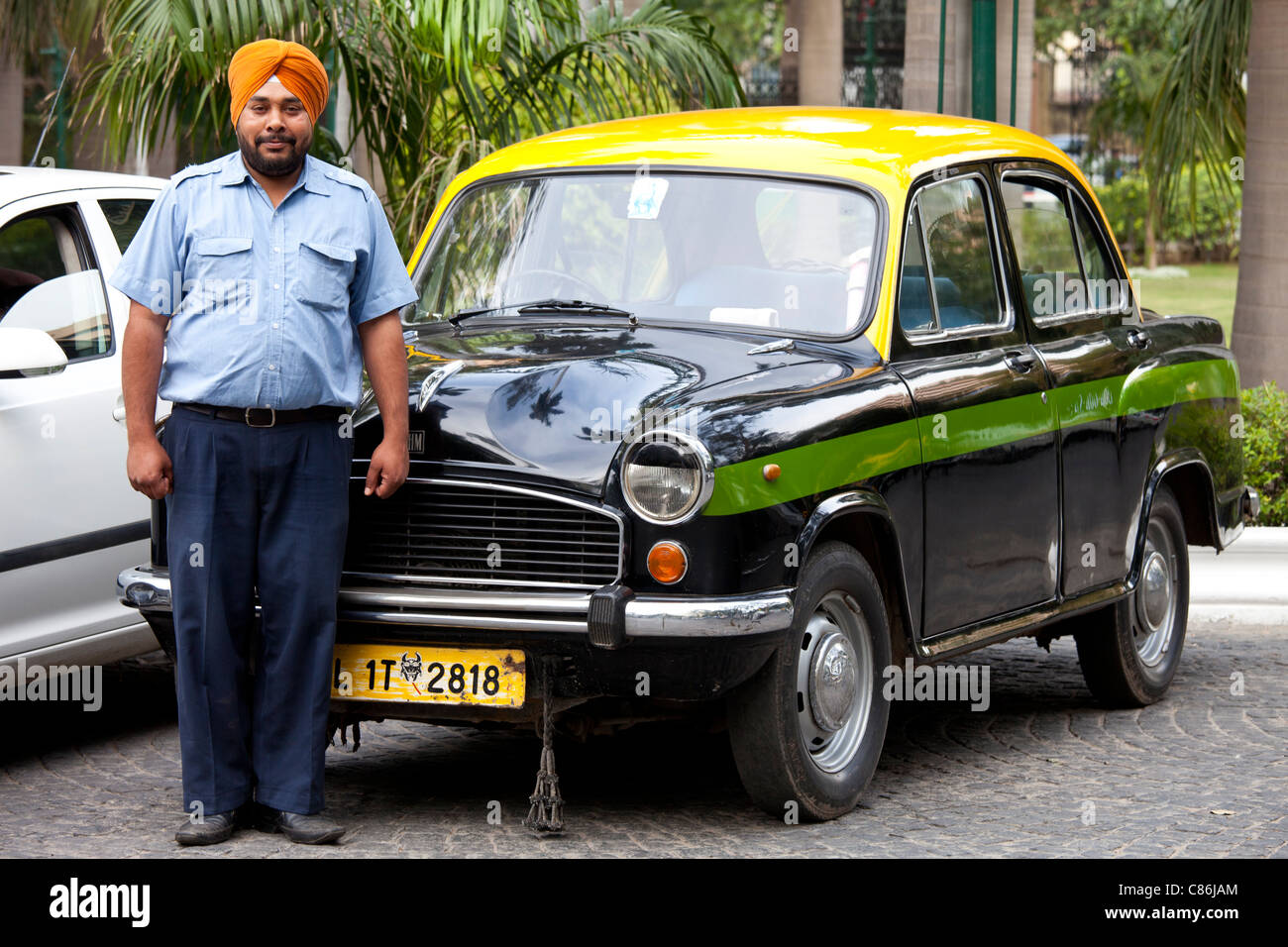 Sikh taxi driver with classic Ambassador taxi at The Imperial Hotel, New Delhi, India - Stock Image