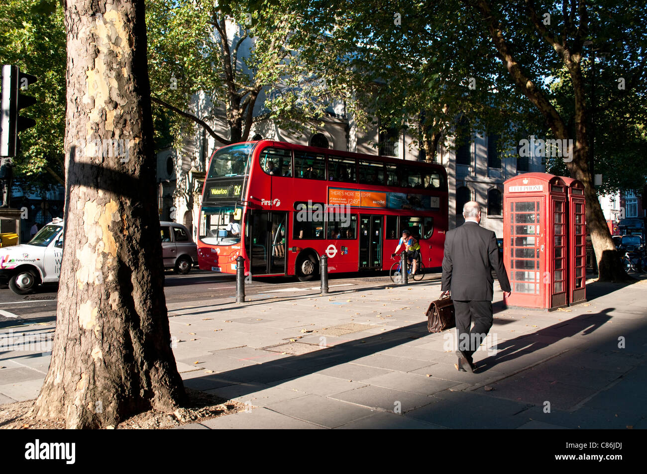 Red bus and telephone box on the Strand, London, United Kingdom - Stock Image