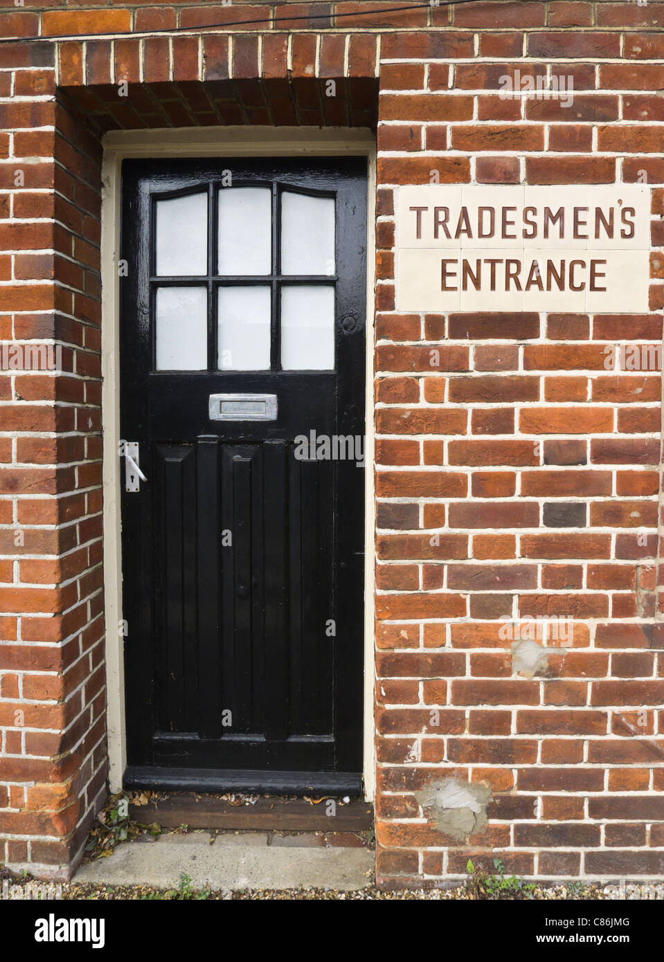 Doorway with a sign saying 'Tradesmen's Entrance.' - Stock Image