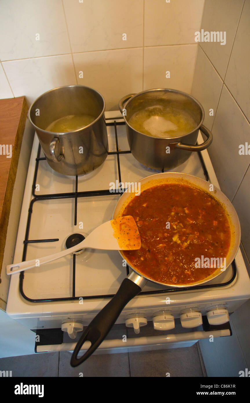 Pasta sauce simmering and pots of pasta being boiled on stove Prague Czech Republic Europe - Stock Image