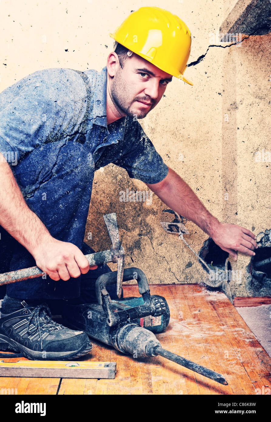 manual worker with hammer at construction site, indoor shot - Stock Image