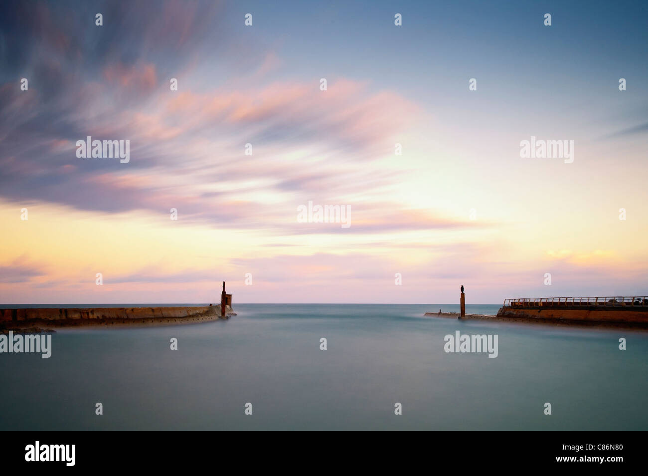 Long exposure of the sunrise over deserted harbor - Stock Image