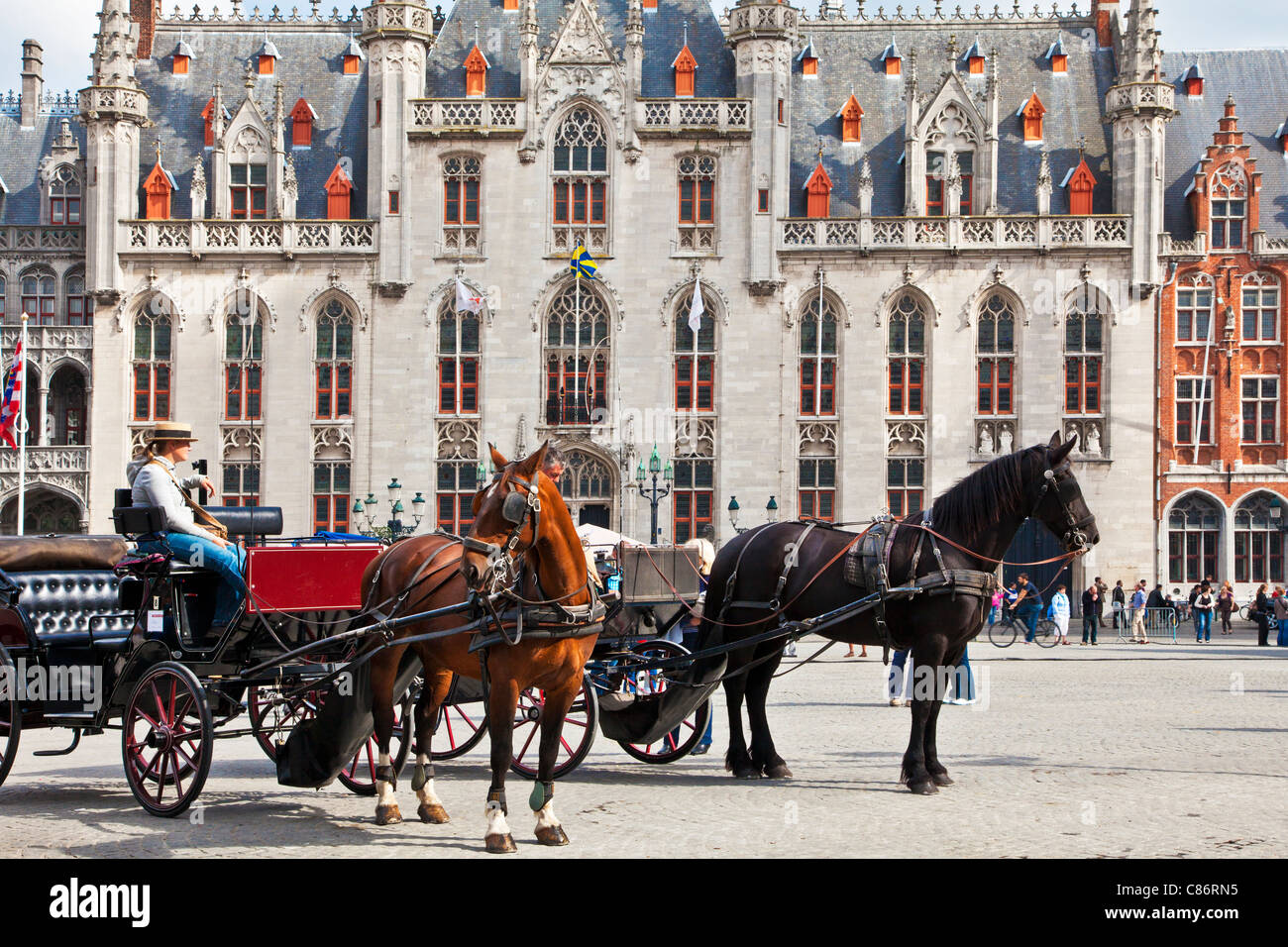 Tourist horse and carriage before the Provincial Court, Provincaal Hof in Grote Markt or Market Square, Bruges (Brugge), - Stock Image