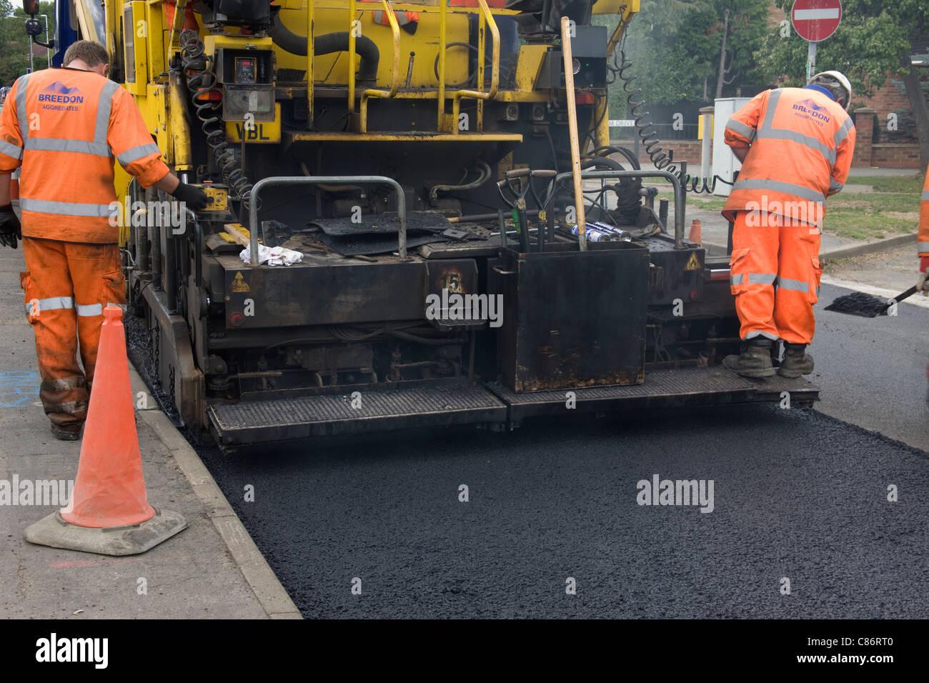 Tarmac machine laying new road surface. - Stock Image