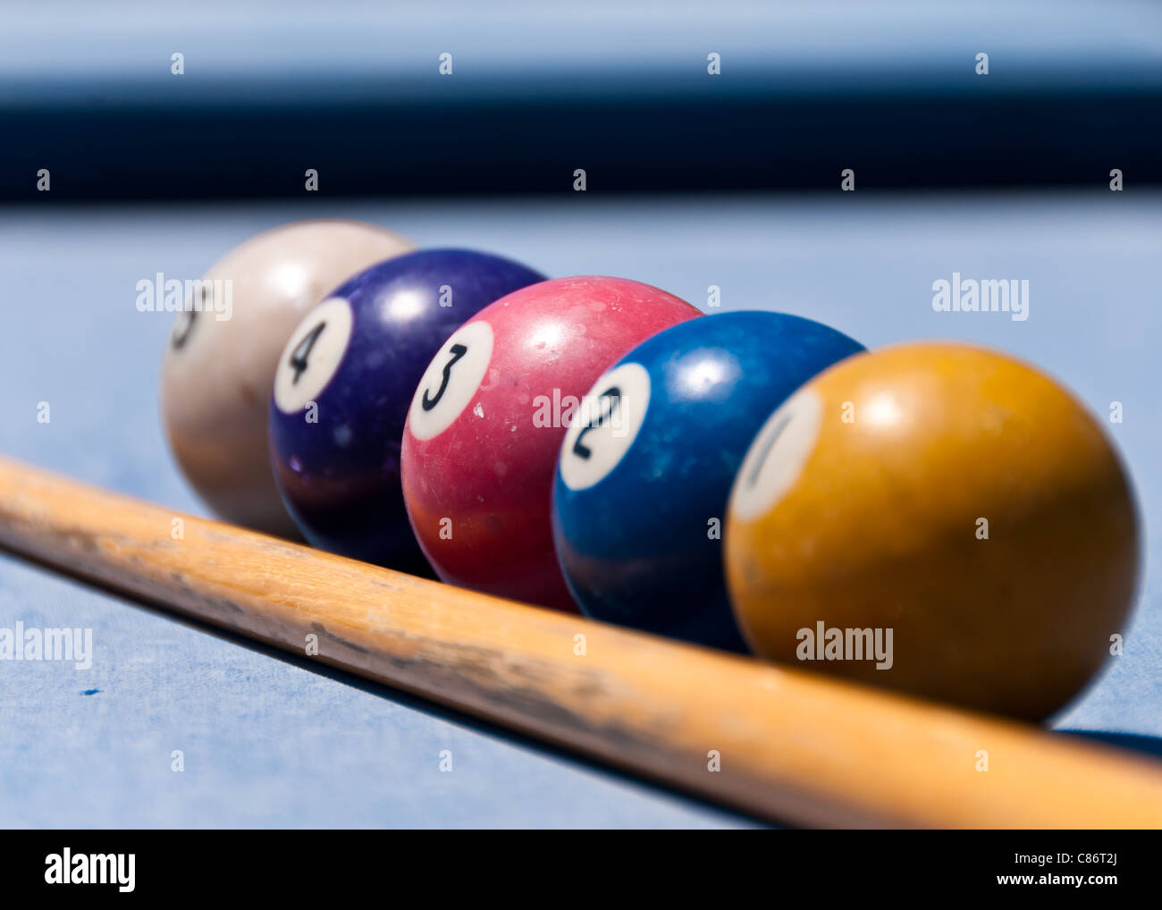 Cue and pool balls on a blue pool table shot outside - Stock Image