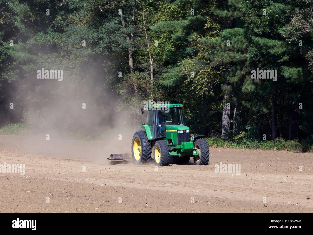 A green John Deere tractor working in a dusty field. - Stock Image
