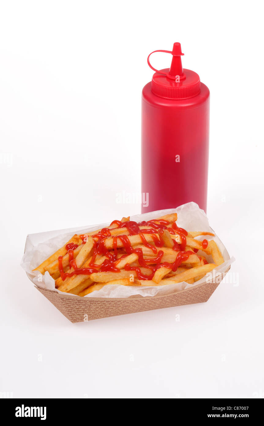 Paper basket of french fries with ketchup over them with a plastic red catsup bottle on white background, cut out. - Stock Image