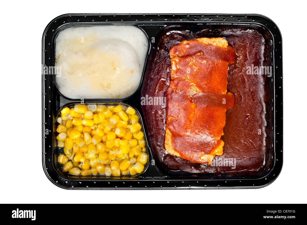 A TV dinner consisting of ribs, mashed potatoes and corn isolated on white - Stock Image