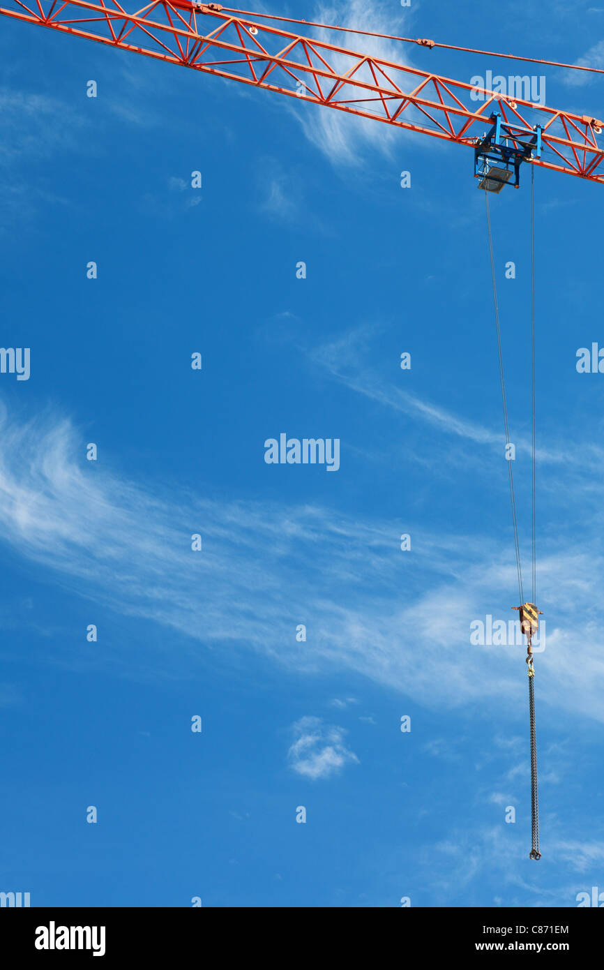 The crane elevating against the blue sky - Stock Image