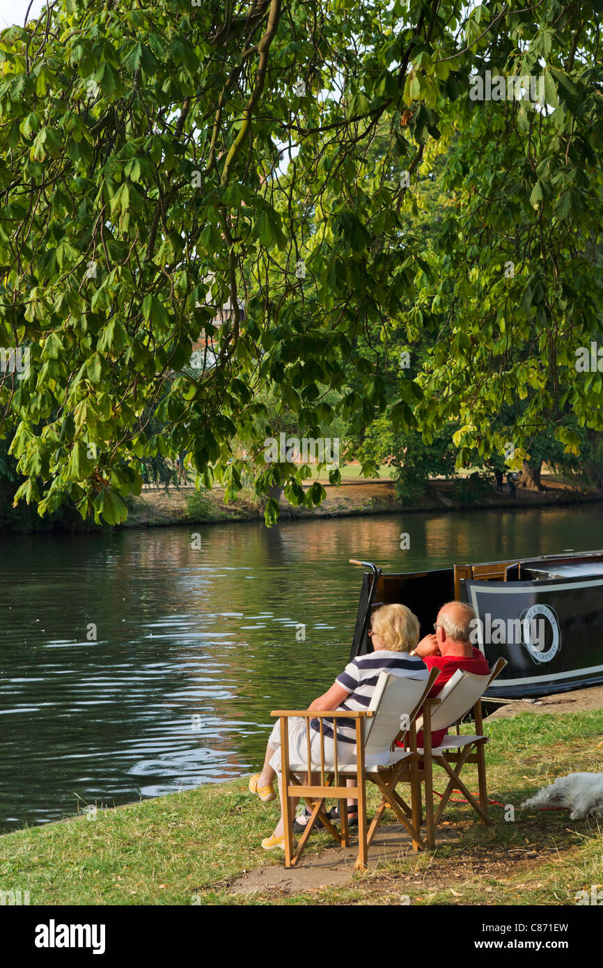 Couple sitting by their narrowboat on banks of River Avon in late afternoon sun, Stratford-upon-Avon, Warwickshire, - Stock Image