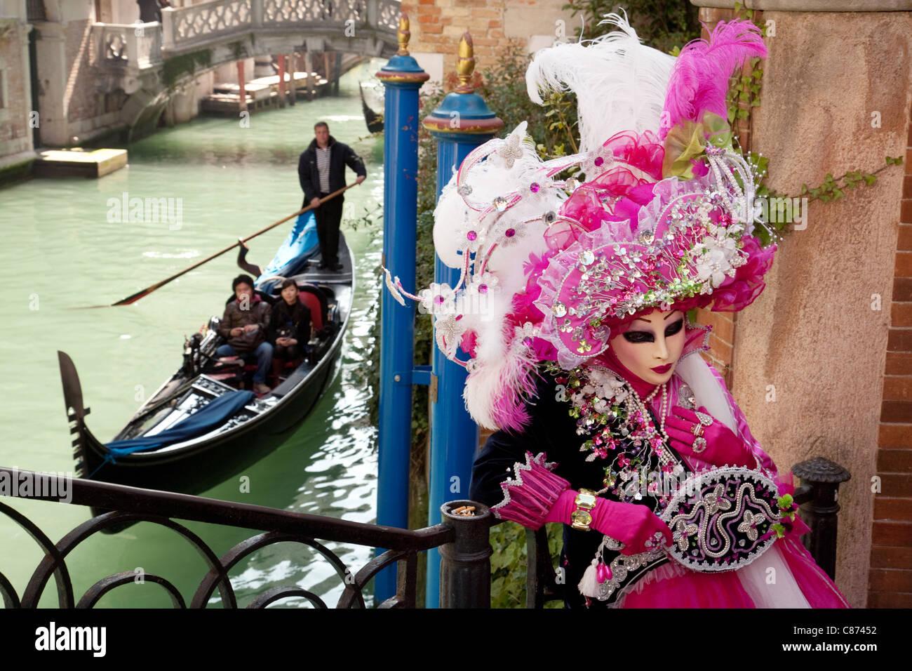 Gondola and masquerader in mask, the Venice Carnival, Venice, Italy Stock Photo