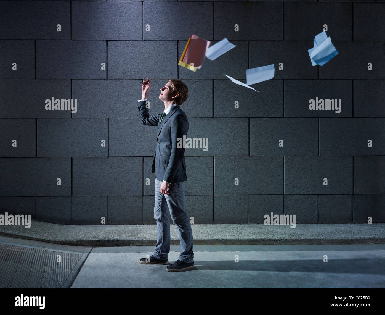 young business man walking out from office parking and throwing away paperworks. Horizontal shape, side view, copy - Stock Image