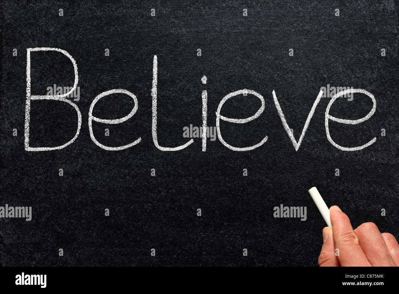 Believe, written with chalk on a blackboard. - Stock Image