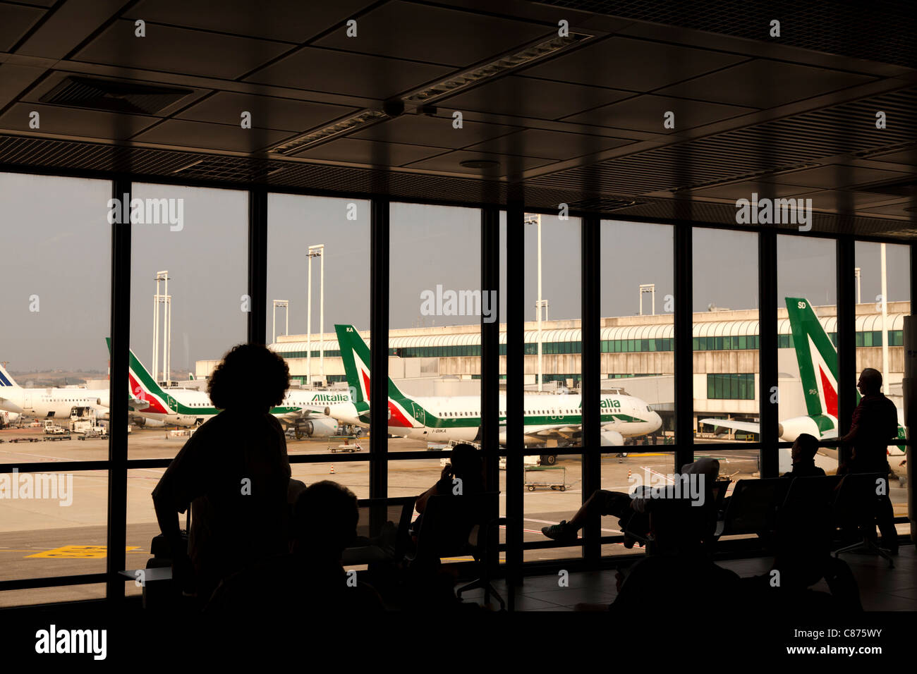 Rome Fiumicino Leonardo da Vinci airport terminal 2 interior silhouetted people and view of runway Passengers waiting - Stock Image