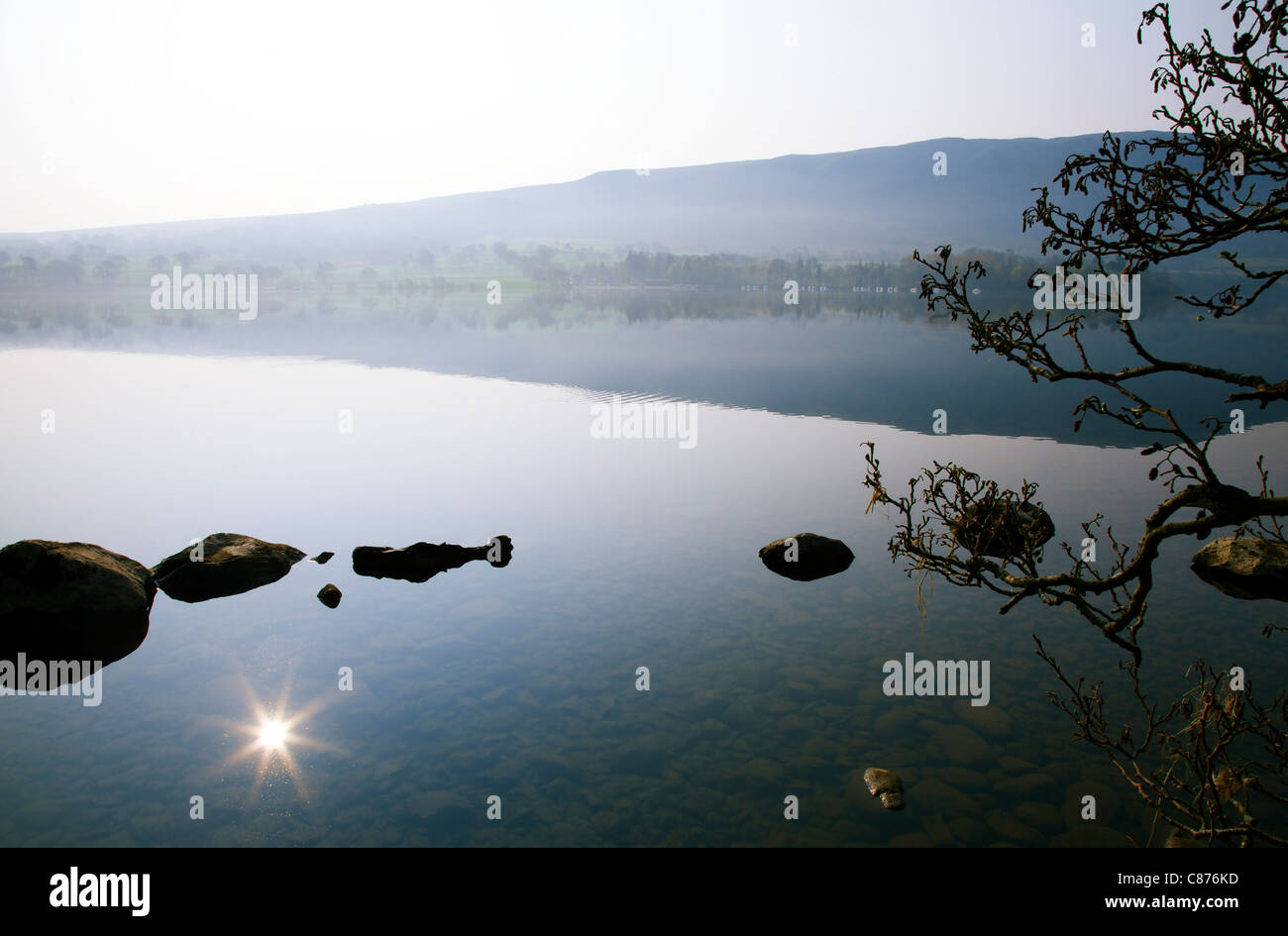 Ullswater lake at dawn with slight mist and flare on reflection of sun in water - Stock Image