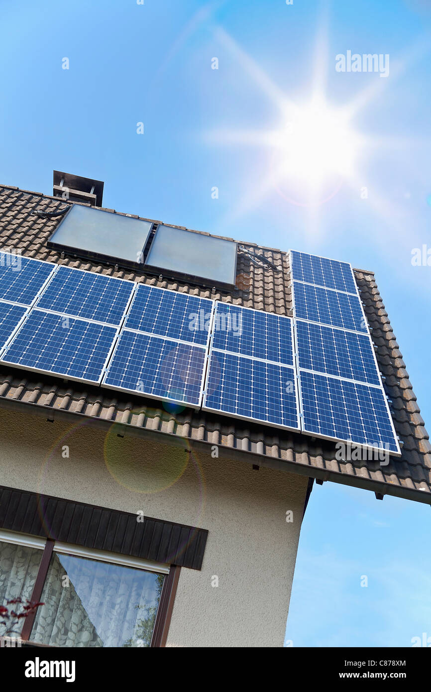 Germany, Cologne, Solar panels on rooftop against blue sky and sun - Stock Image