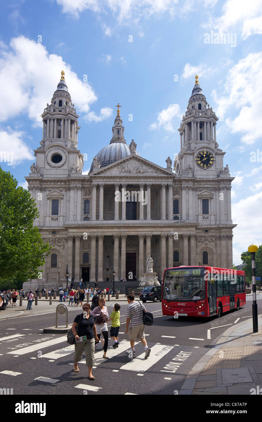Red bus and pedestrians on crossing outside St Paul's Cathedral, City of London, England, UK, United Kingdom, - Stock Image