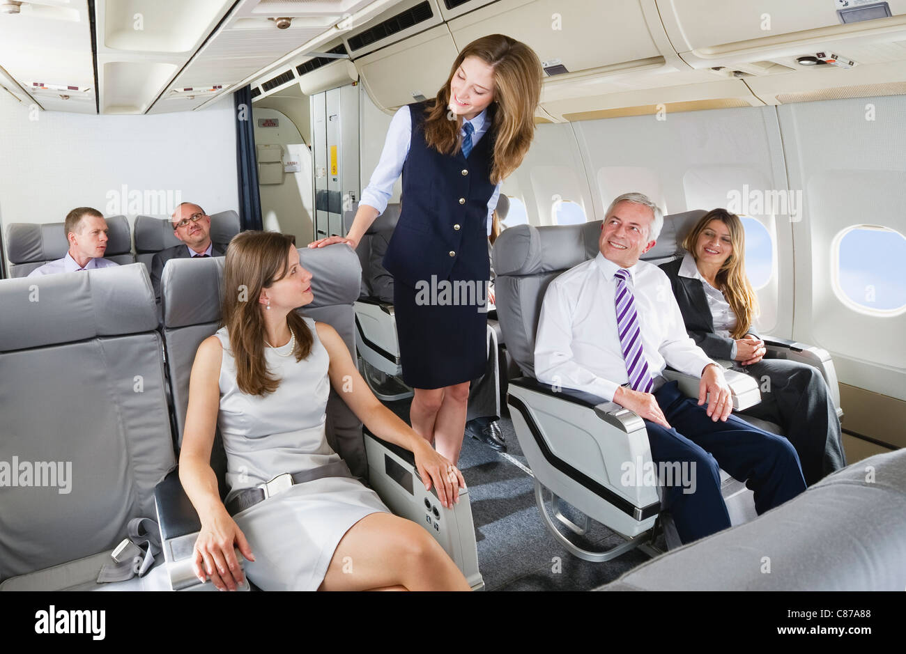 Germany, Bavaria, Munich, Stewardess and passengers in business class airplane cabin, smiling - Stock Image