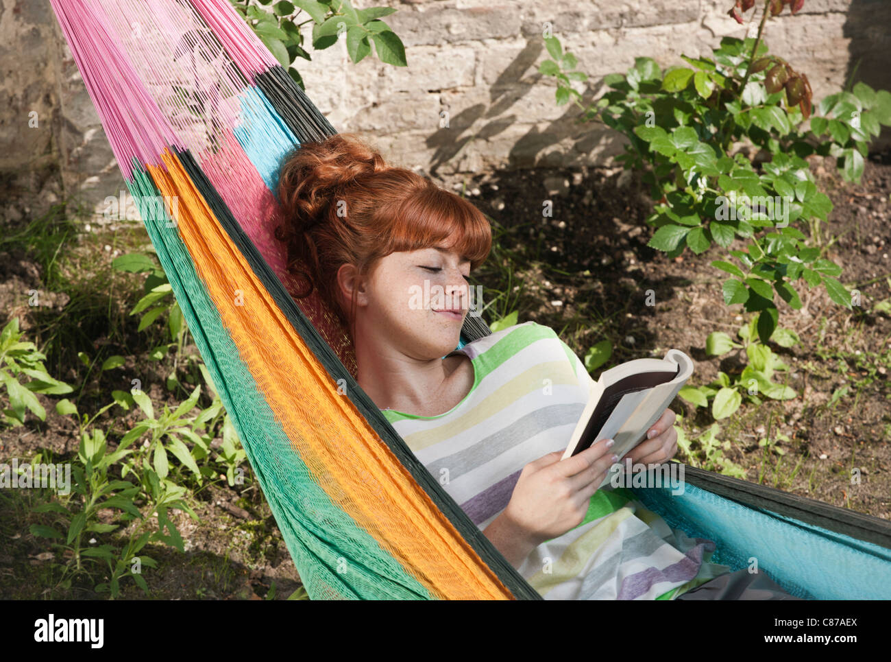 Germany, Berlin, Young woman reading book in hammock, smiling - Stock Image
