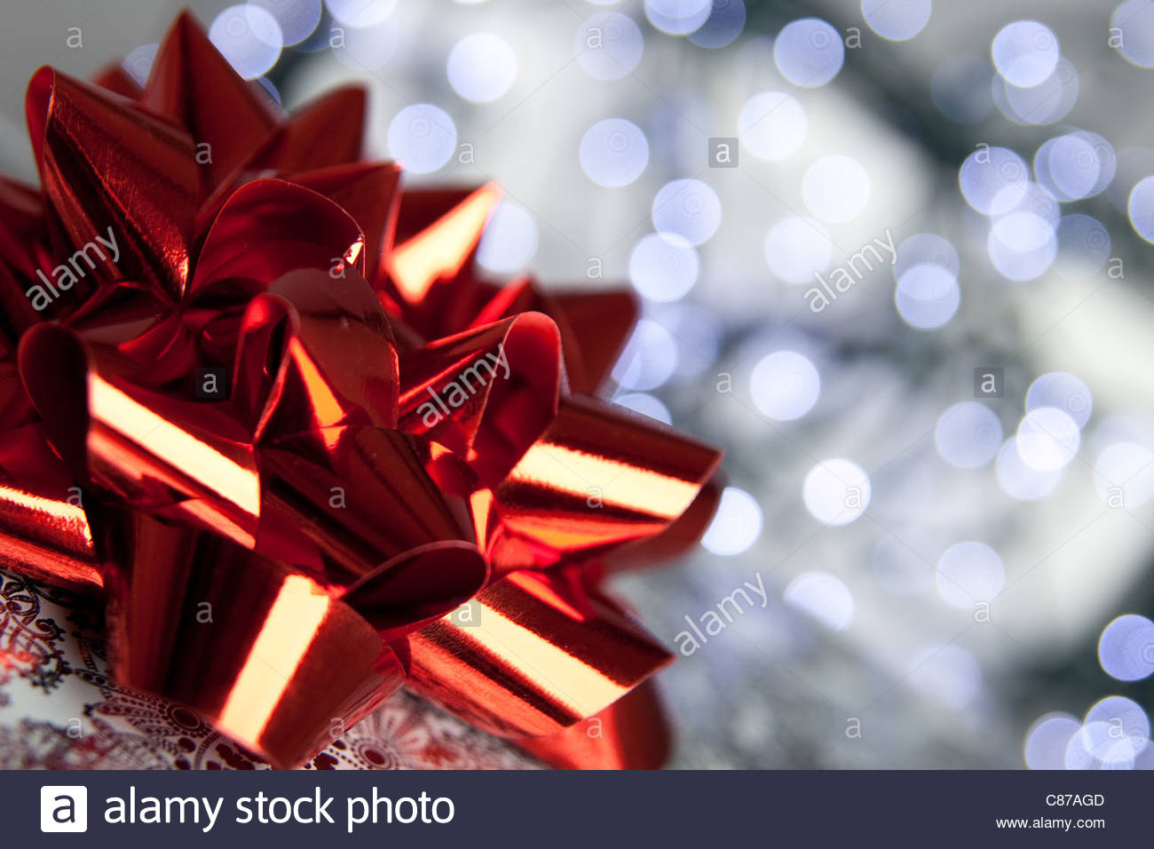 A close view of a red bow on top of a Christmas present, against a background of fairy lights - Stock Image