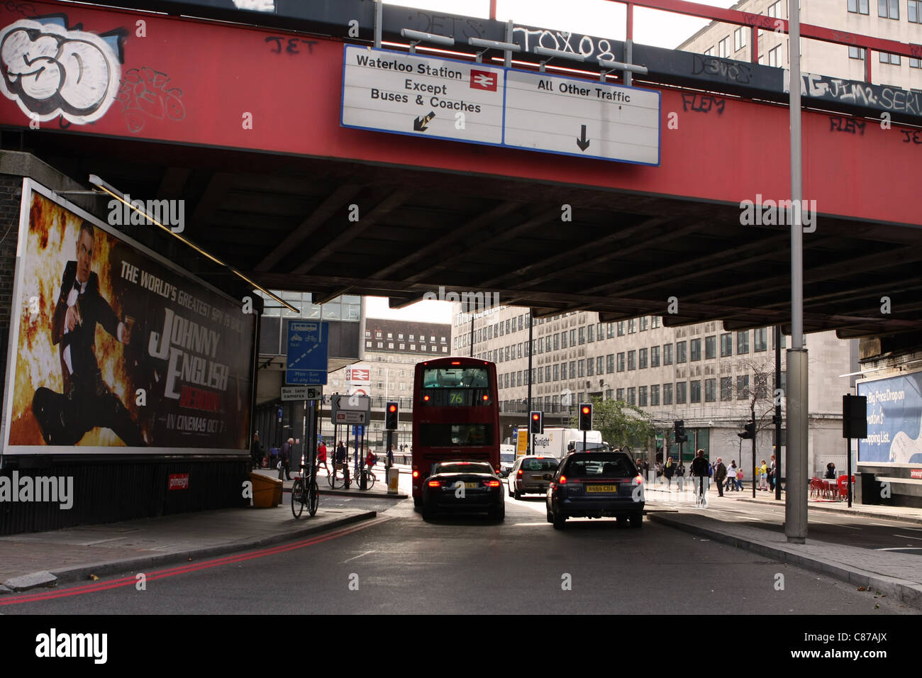 a bus and cars waiting under a bridge for traffic lights to change from red to green Stock Photo