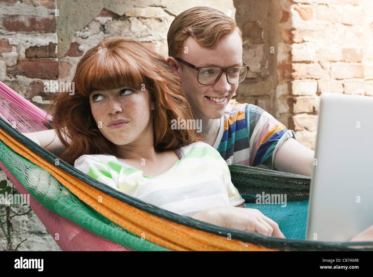 Germany, Berlin, Young woman using laptop in hammock with young man beside her Stock Photo