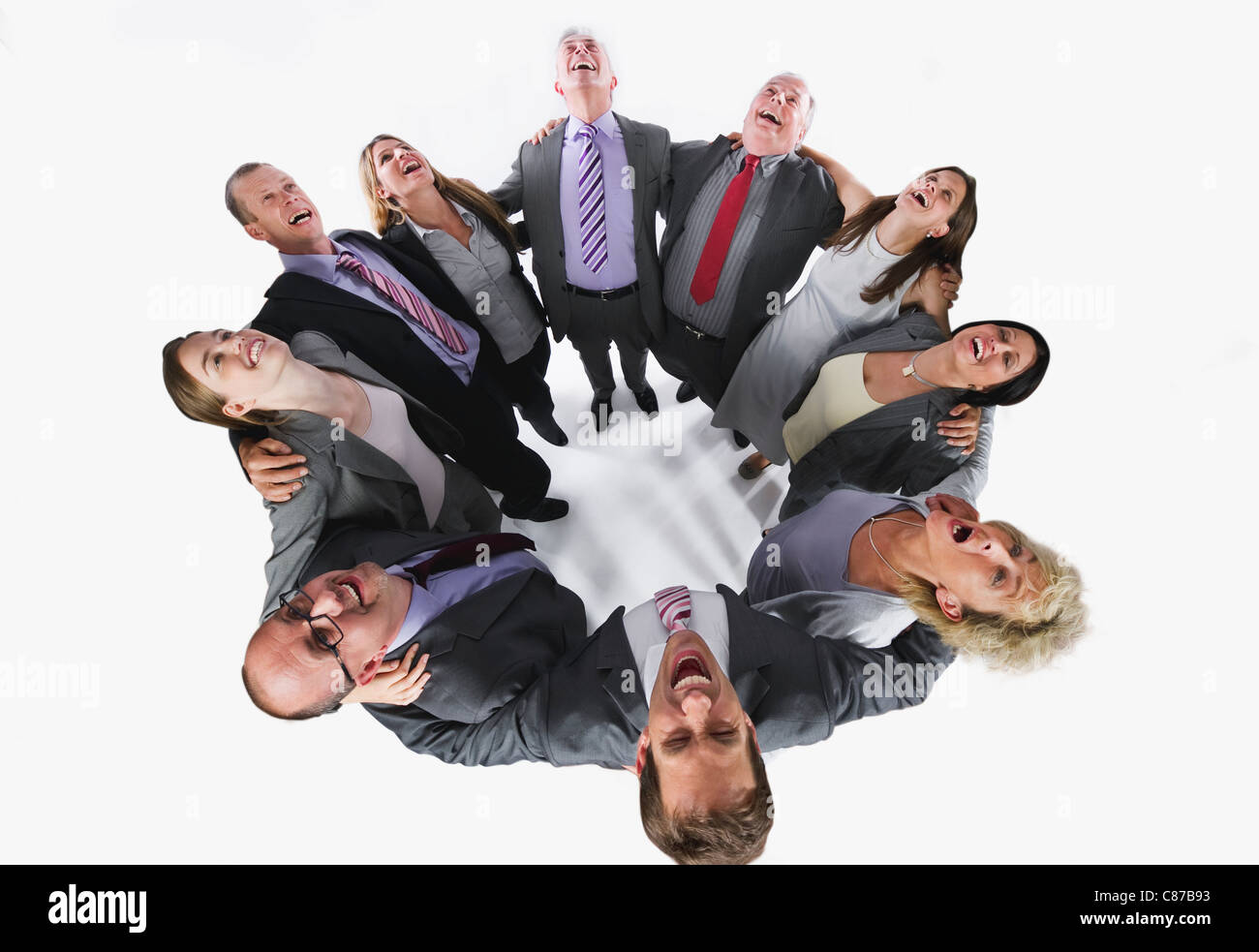 Business people forming huddle and looking up against white background - Stock Image