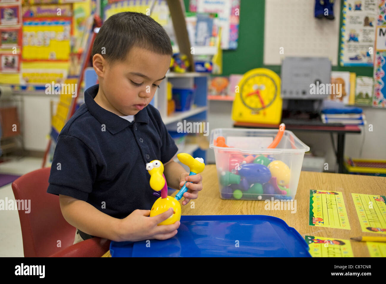 4 year old Caucasian preschool boy playing with a toy on a table in the school classroom, - Stock Image
