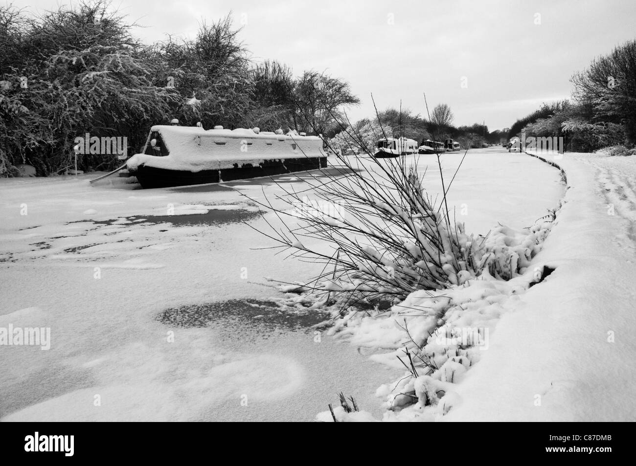 Frozen Grand Union canal and boats under snow in winter in Cosgrove, Northamptonshire, near Milton Keynes - Stock Image