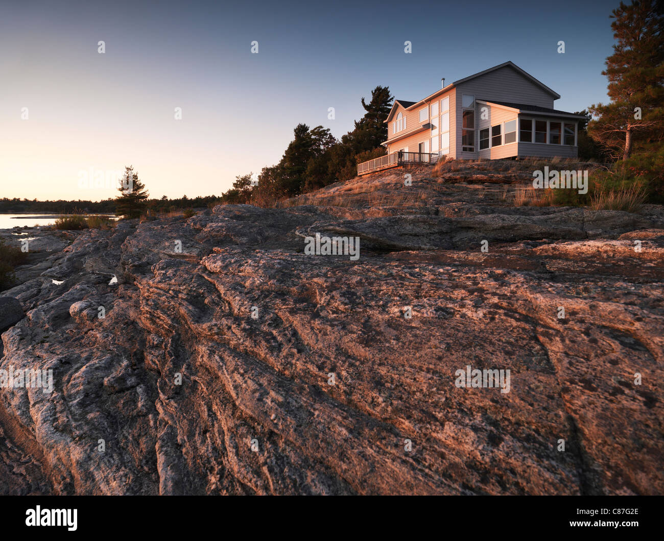 Sunset scenery of a cottage house on a beautiful rocky shore - Stock Image