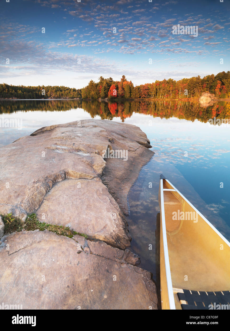 Canoe at a rocky shore of lake George. Beautiful sunset fall nature scenery. Killarney Provincial Park, Ontario, Stock Photo