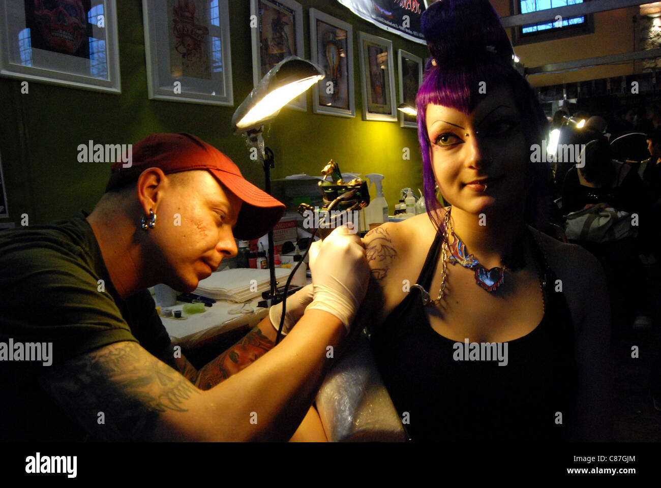 A man tattooing a cemetary scene on the arm of a woman Stock Photo