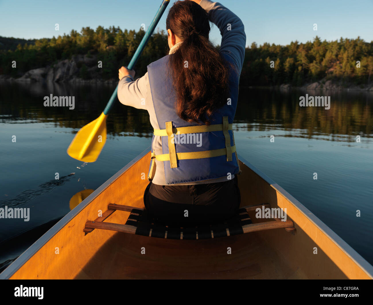 Woman paddling a canoe. Sunset fall nature scenery. Killarney Provincial Park, Ontario, Canada. - Stock Image