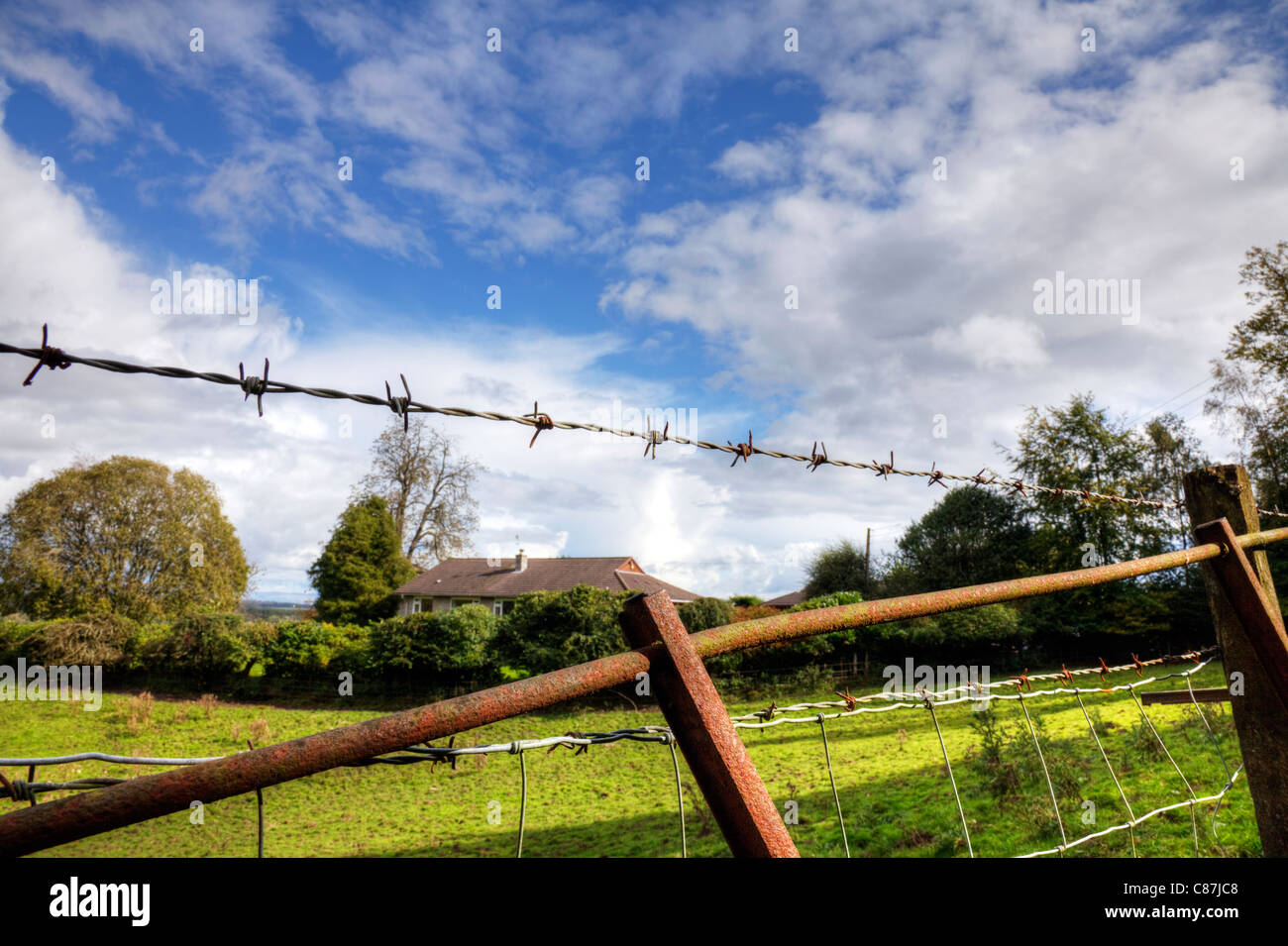 Close detail of a barb, barbed wire fence above an old rusty gate in front of a field in Gartmore, Scotland, Trossachs - Stock Image
