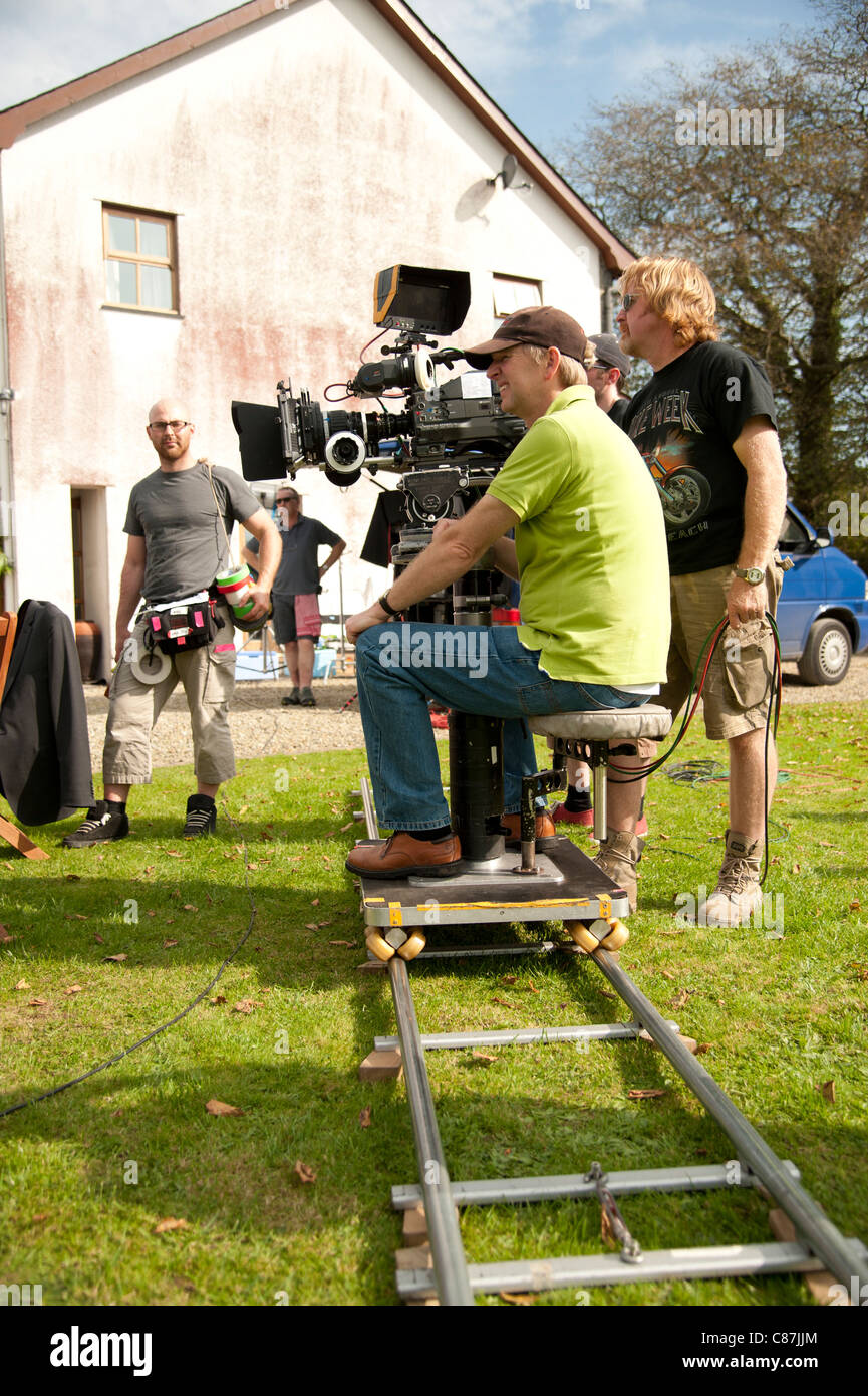 A camera crew working on the location recording of a television drama series, UK - camera on a dolly and tracks - Stock Image