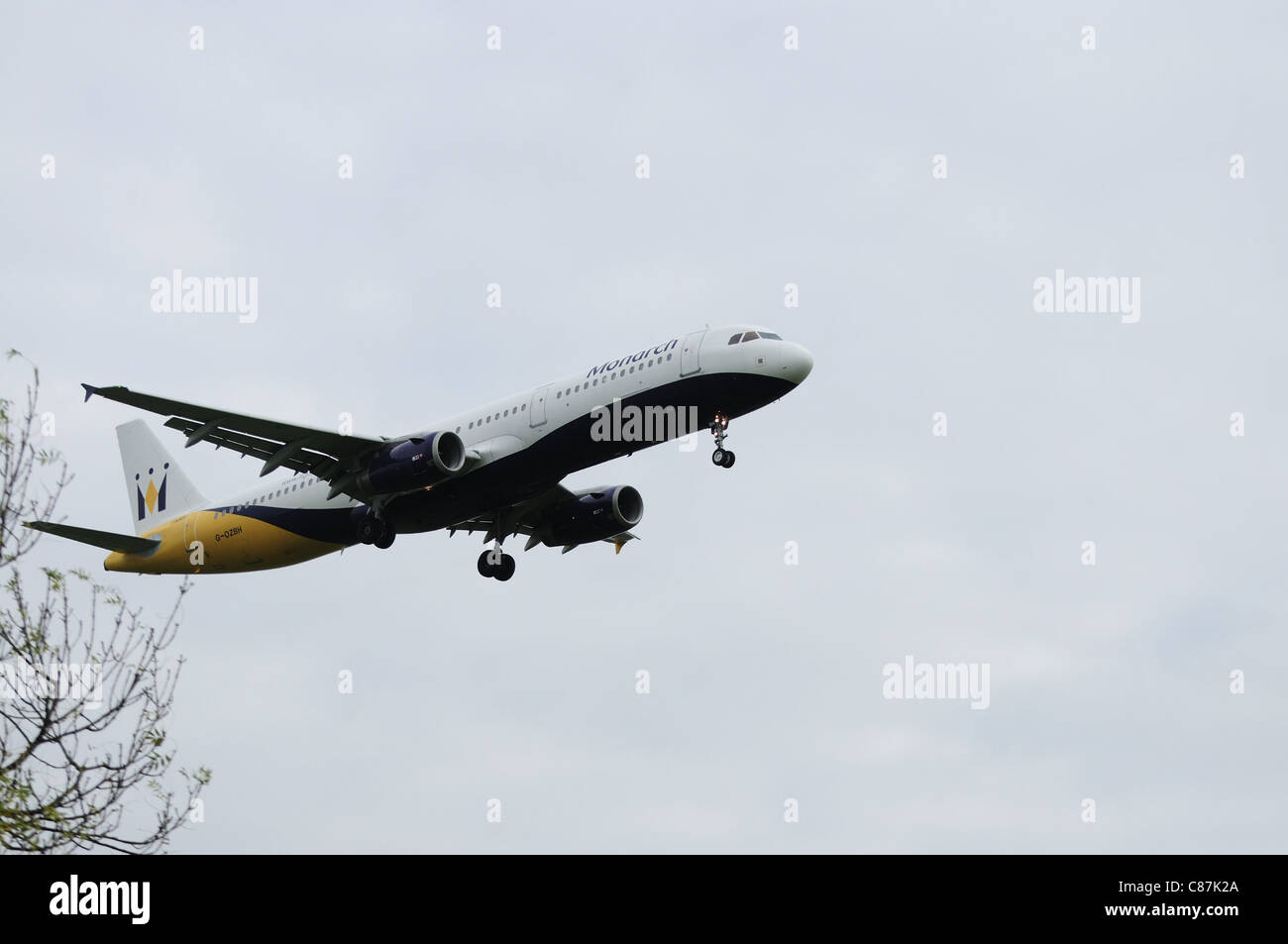 Twin jet aircraft in Monarch airline livery landing at Manchester Airport. - Stock Image