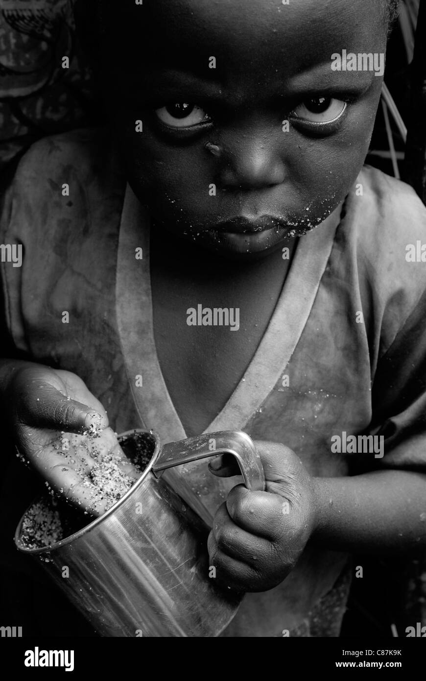 A displaced Congolese toddler eating in an IDP camp in North Kivu province in eastern Democratic Republic of Congo - Stock Image