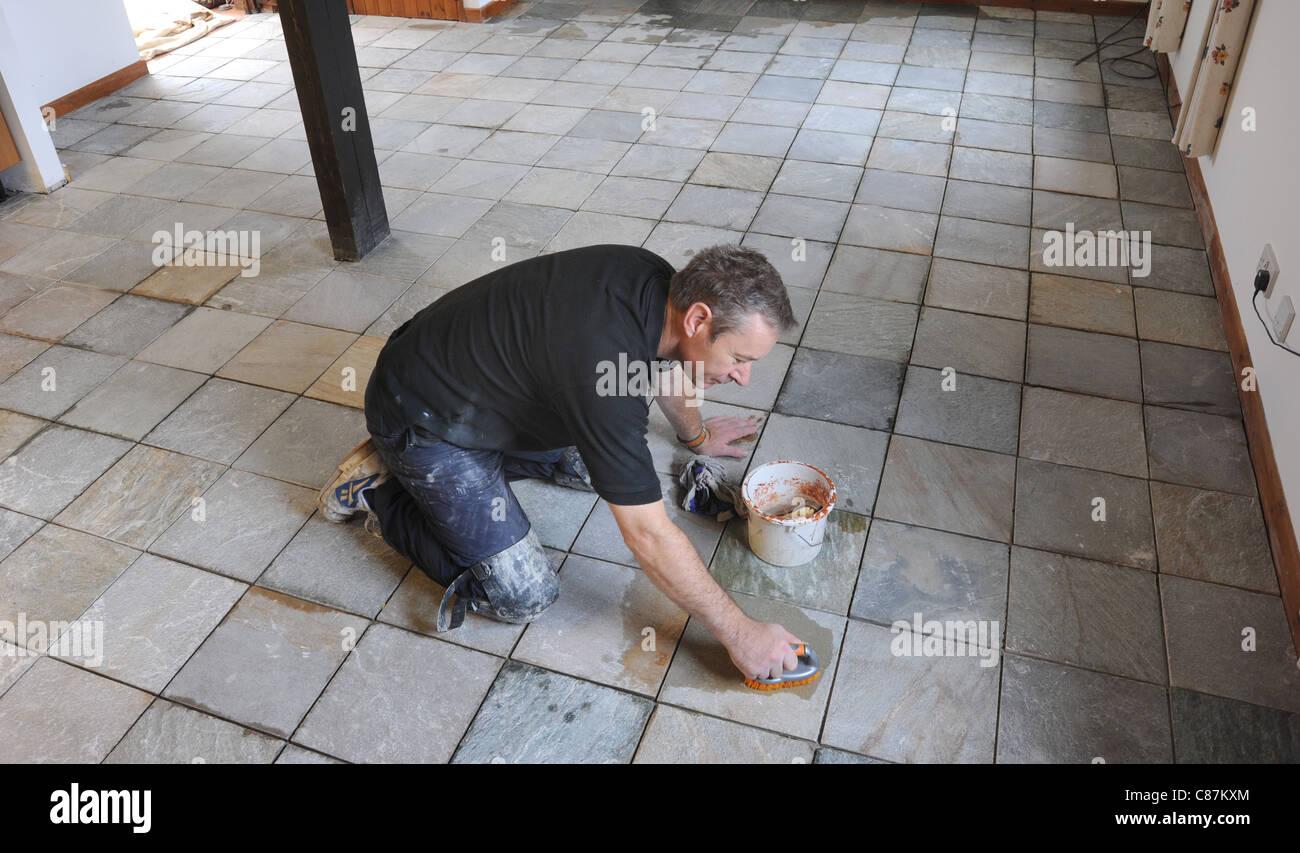 TRADESMAN WORKING ON KNEES ON A  REAL SLATE FLOOR TILES RE HOUSE IMPROVEMENTS DIY FLOOR TILES FLOORING HOMES CLEANING - Stock Image