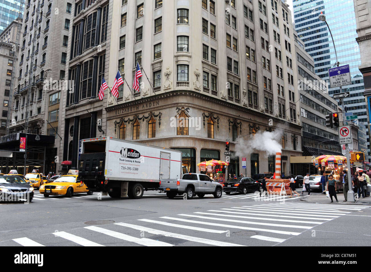View East 56th Street 5th Avenue road-crossing, yellow taxis, cars, white van, people, red white plastic steam vent, - Stock Image