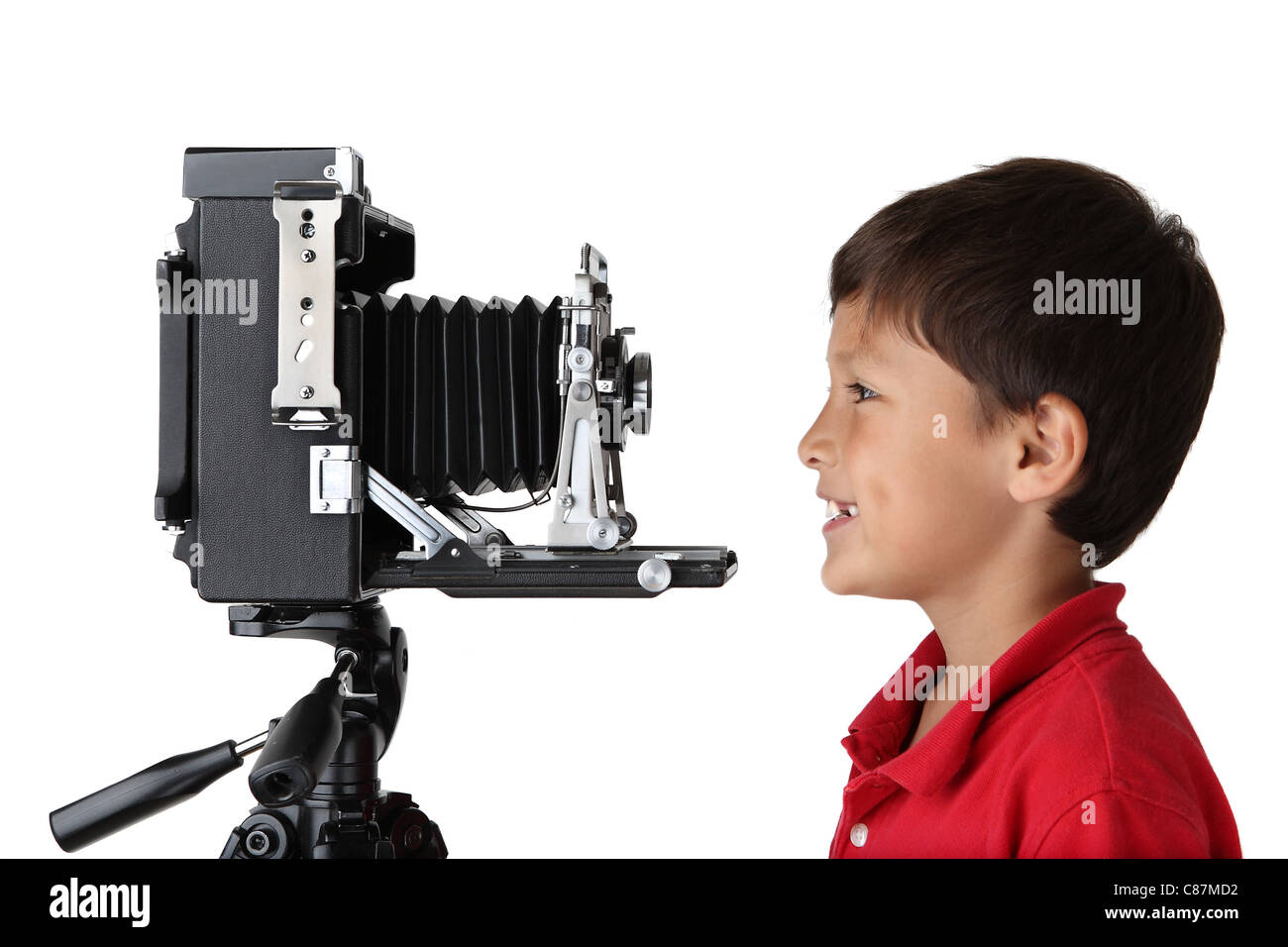 Happy smiling boy in red shirt looking into old press camera on white background - Stock Image
