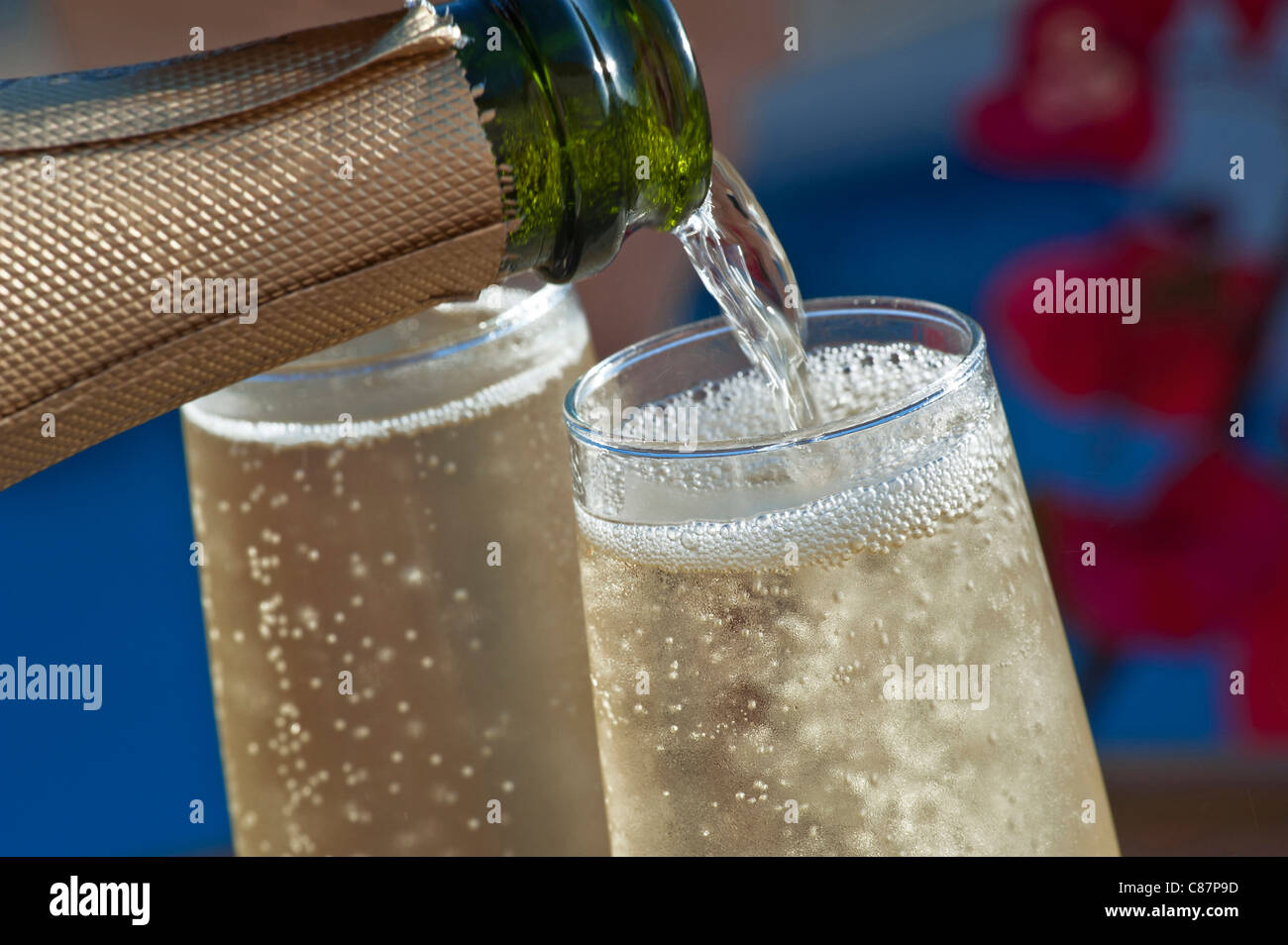 Close view on pouring chilled glasses of champagne on sunlit terrace with colourful Bougainvillea flowers and pool - Stock Image