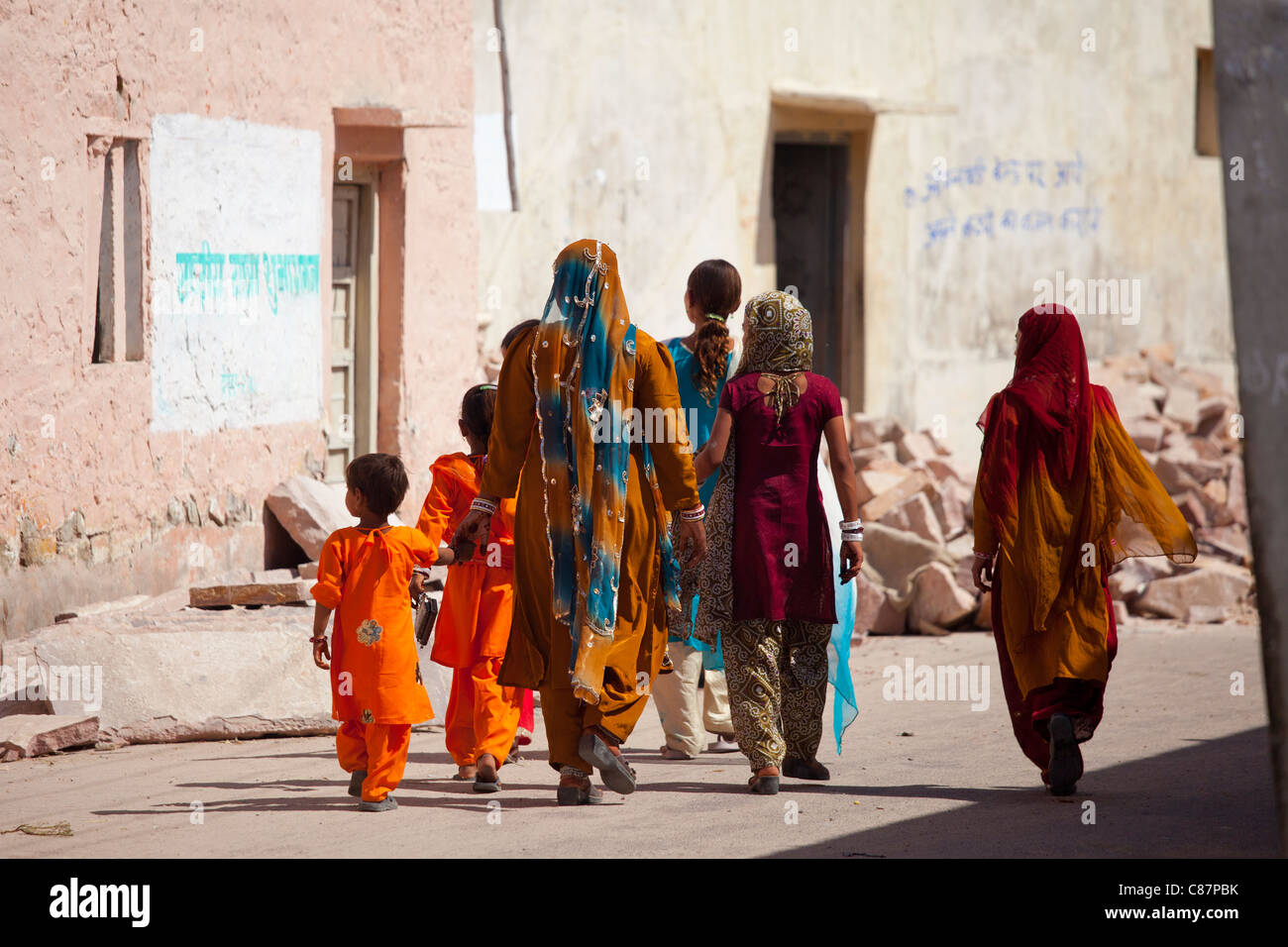 Indian women and girls dressed as wedding guests walking to the wedding in village of Rohet in Rajasthan, Northern - Stock Image