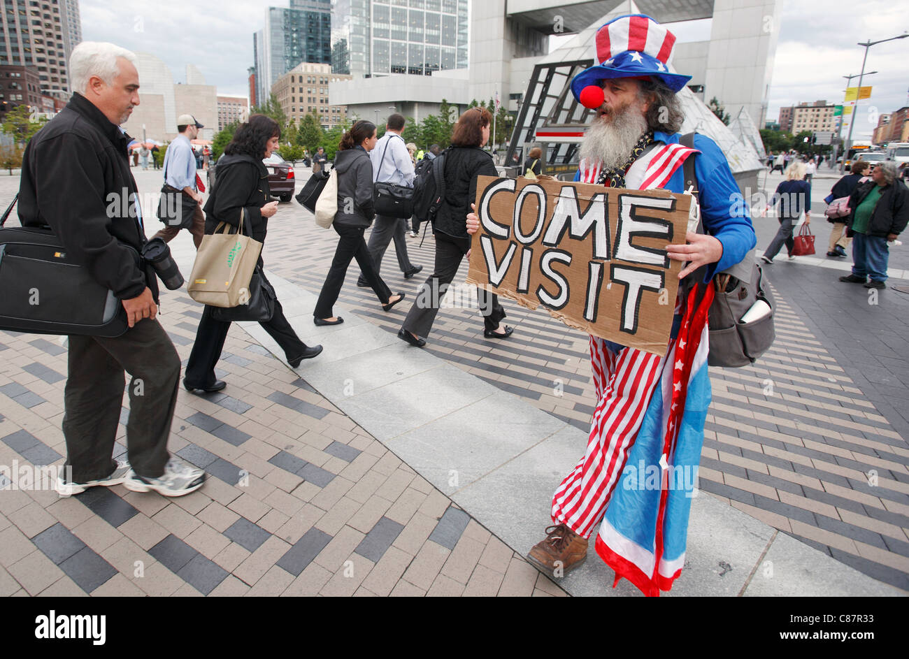 An Occupy Boston demonstrator protests in downtown Boston, Massachusetts, as commuters head home. - Stock Image