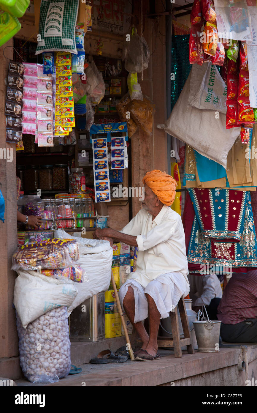 Indian shopkeeper in his food shop and general store in village of Rohet in Rajasthan, Northern India - Stock Image