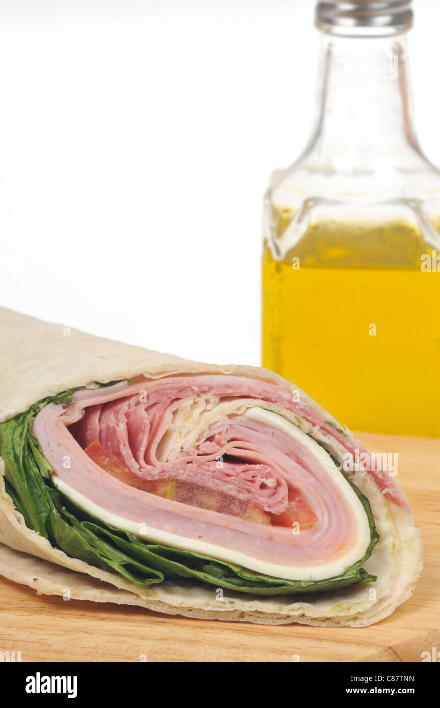 Italian deli meat wrap sandwich with lettuce, cheese & tomato and bottle of olive oil on white background. USA - Stock Image
