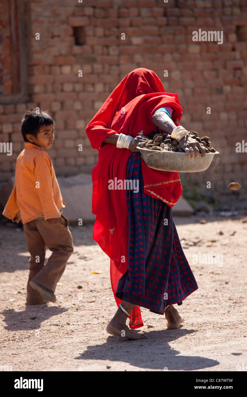 Indian woman with her child carries horse manure pats to dry for cooking fuel in Khore village, Rajasthan, Northern Stock Photo